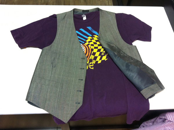 A printed purple t-shirt is paired with a men's suit vest