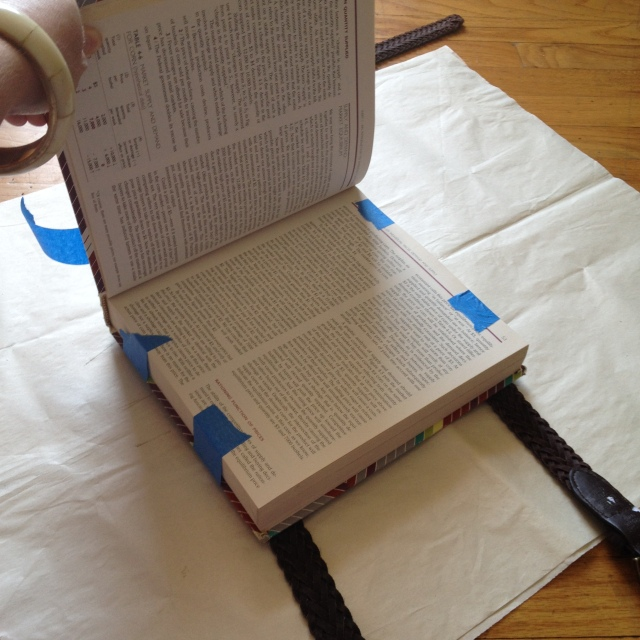 Step 3: Blue tape the belts over the L brackets on the bottom of the book.  Open the book to the desired page and wrap the blue tape around.