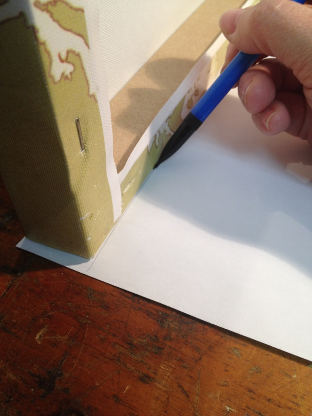 Step 1-Place canvas on its side and draw a cut line on the backside of the scrapbook paper