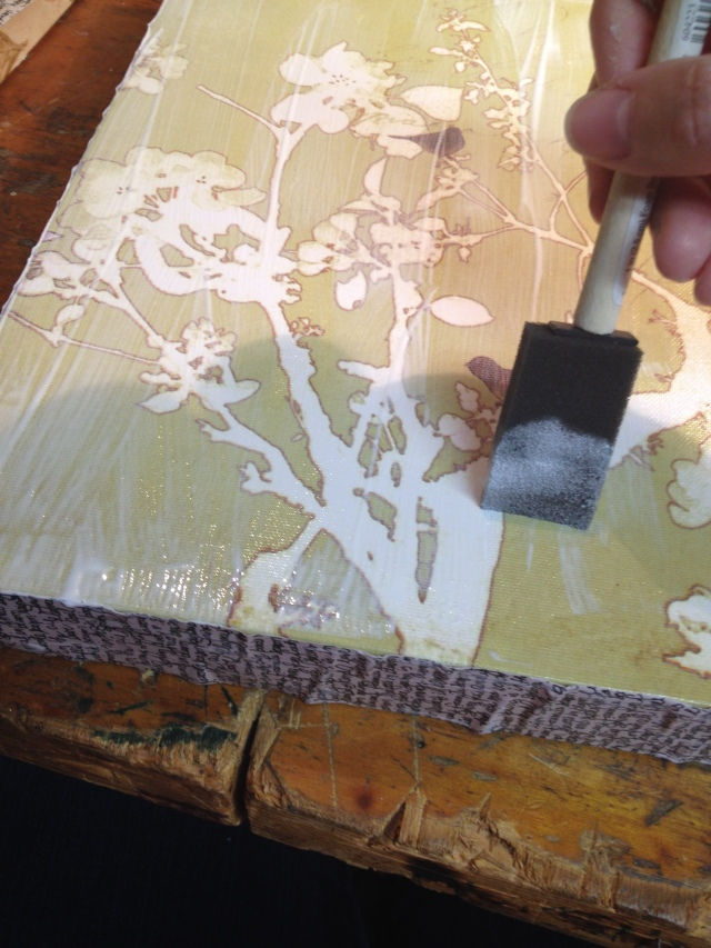 Step 8-Apply decoupage medium to the front of the canvas, place paper on top, & rub flat